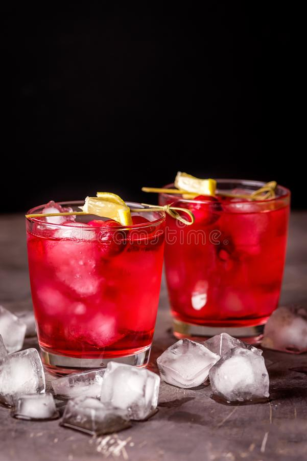 Two Glasses of Berries Cold Drink Tasty Cranberry Lemonade with Ice Dark Photo Black Background Vertical stock images