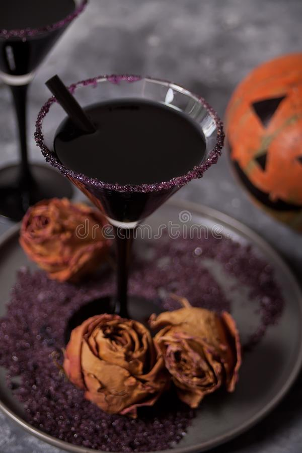 Two glasses with black cocktail, dried roses, Jack-o`-lantern for Halloween party on the dark background.  royalty free stock image