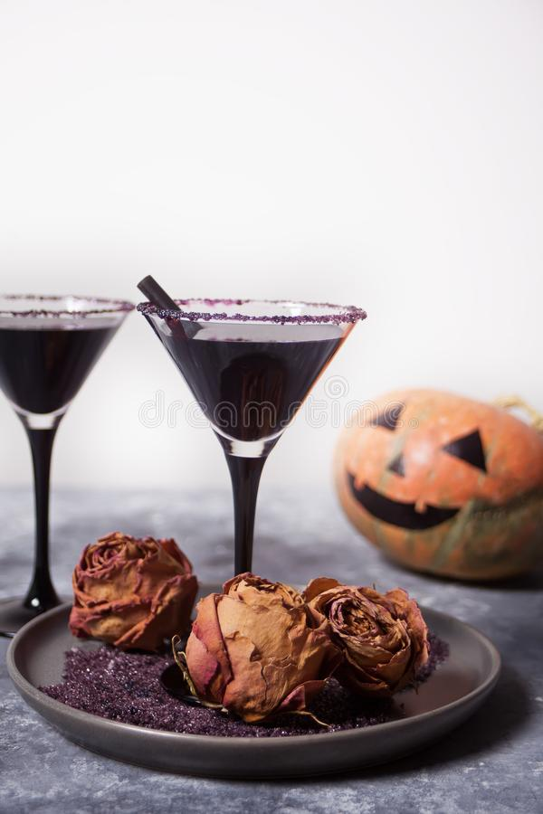 Two glasses with black cocktail, dried roses, Jack-o`-lantern for Halloween party on the dark background. Two glasses with black cocktail, dried roses and Jack-o stock image