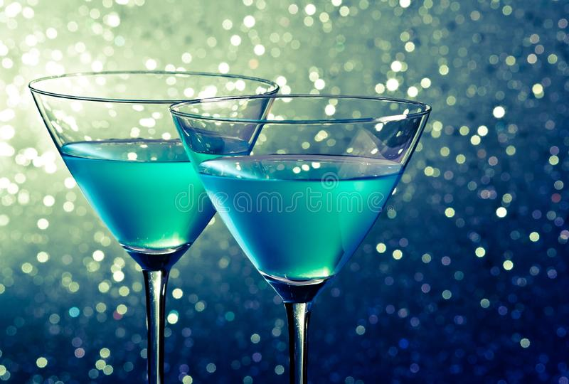Two glasses of blue cocktail on dark green tint light bokeh. Background on table stock photo