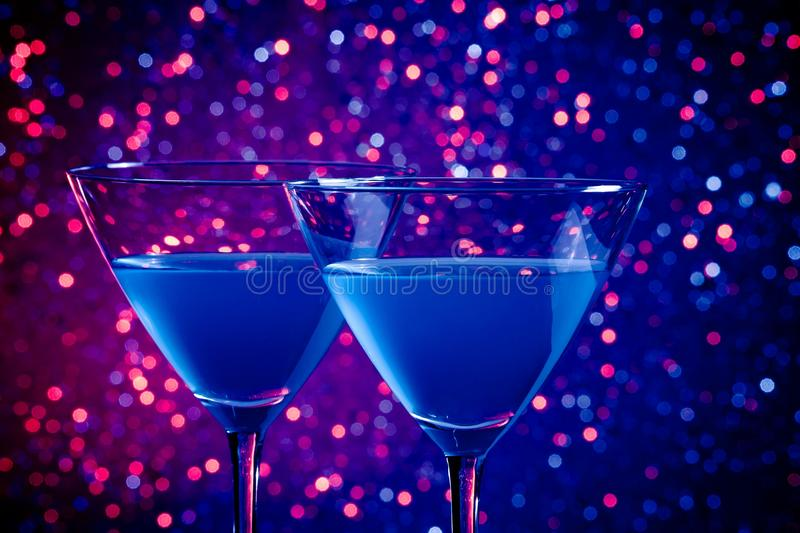 Two glasses of blue cocktail on table. Two glasses of blue cocktail on blue and violet tint light bokeh background stock photo