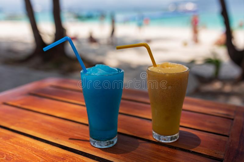 Two glasses with a blue and orange cocktail stand on a wooden table under the rays of the sun. royalty free stock images