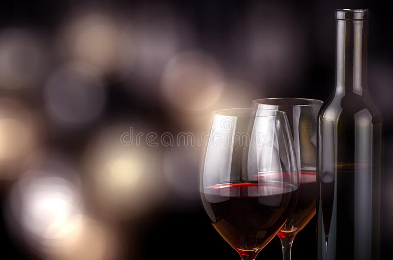 Two glasses and bottle with red wine on bright background stock image