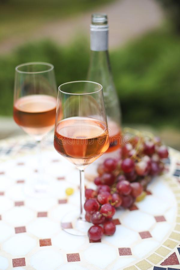 Two glasses and bottle of rose wine in autumn vineyard on marble table royalty free stock photo