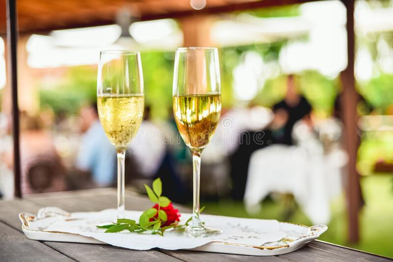 Two glasses of bubbly champagne with unfocused background of a celebration.  royalty free stock photography