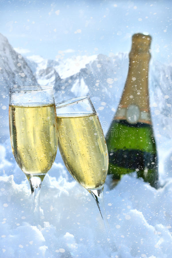 Two glasses of champagne with bottle in snow royalty free stock photo