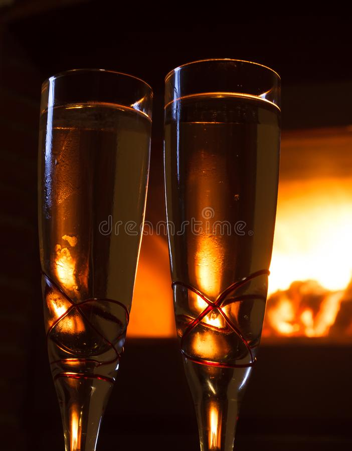 Two glasses of champagne close up in front of fire royalty free stock image