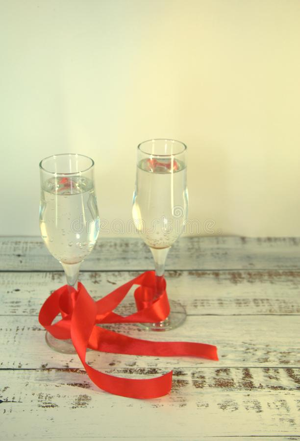 Two glasses with champagne, connected by a scarlet satin ribbon on a wooden table stock photos