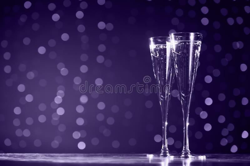 Two glasses of champagne on dark bokeh background. Ultra violet. Two glasses of champagne on dark bokeh background. Holiday concept. Festive bokeh background royalty free stock photos