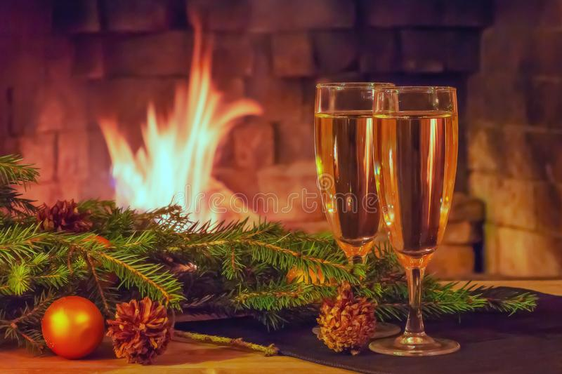 Two glasses of champagne, decorations, Christmas tree branches and a candle on a wooden table in front of a burning fireplace.  royalty free stock image