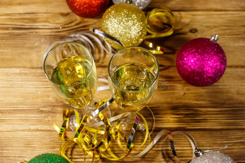 Two glasses of champagne and festive Christmas decorations on wooden table. Top view. Christmas and New Year celebration stock images