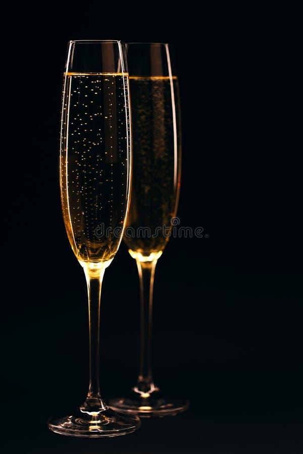 Two glasses of champagne full size on black background. Two glasses of champagne full size on black elegant background. Celebration concept stock image
