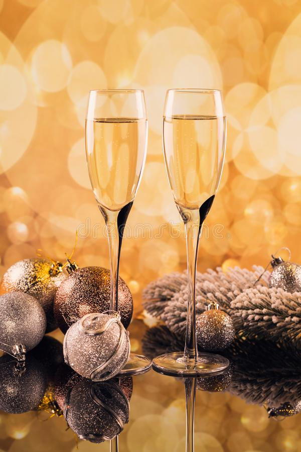 Two glasses of champagne with golden light bokeh on background stock images