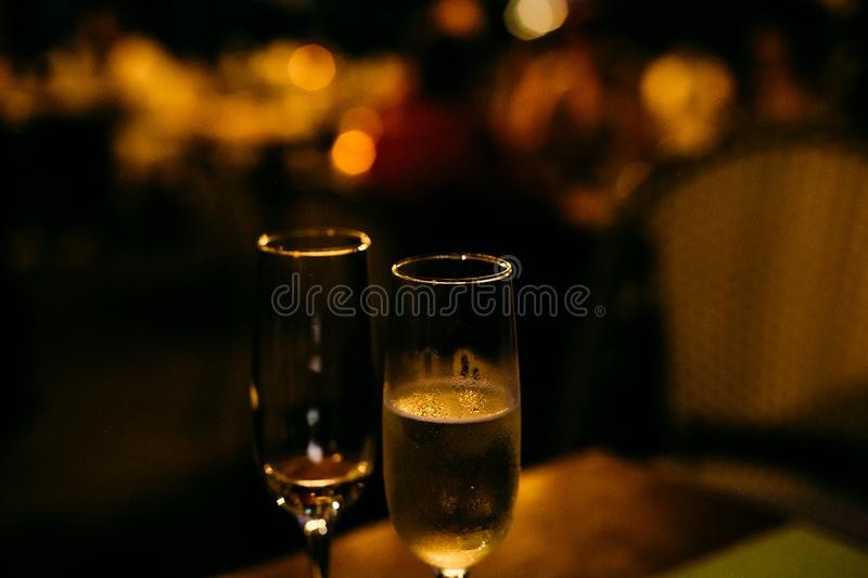Two glasses champagne holiday background with garlands. Two glasses with champagne on a holiday background with garlands, fizz, christmas, new, year, celebrate stock photo
