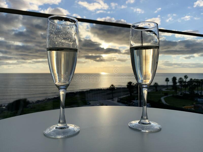 Two glasses of champagne at hotel balcony with view of sea and skyline, luxury romantic dinner for couple. Romantic holiday stock images