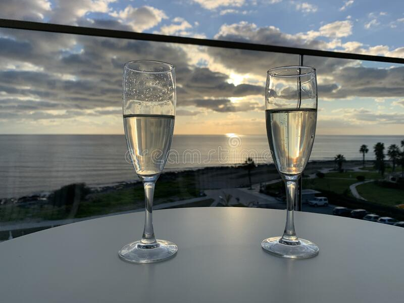 Two glasses of champagne at hotel balcony with view of sea and skyline, luxury romantic dinner for couple. Romantic holiday stock photos