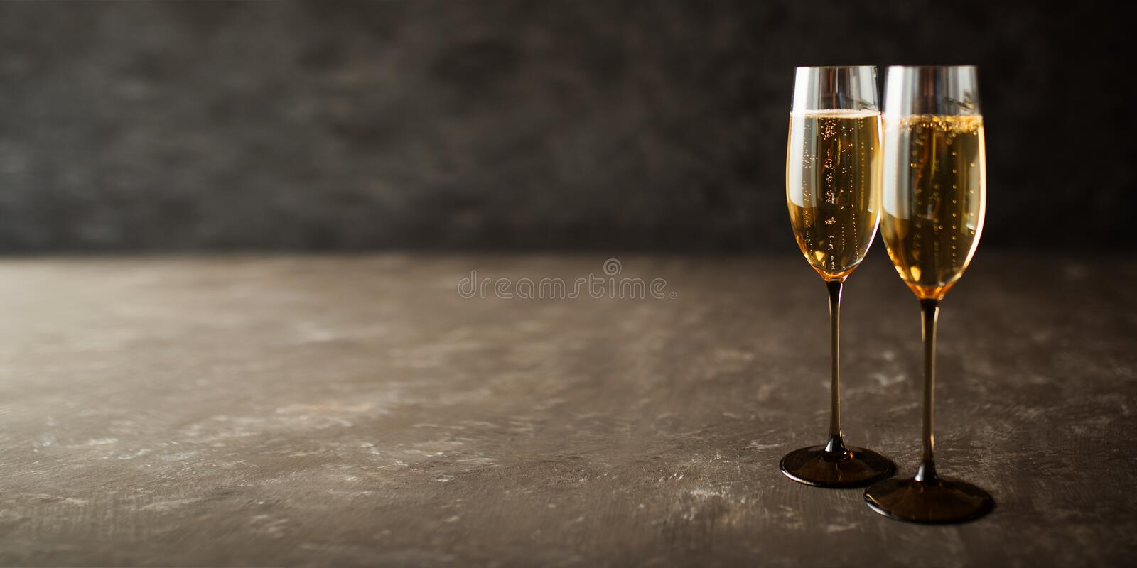Champagne on old gray stone plate. Two glasses with champagne on old gray stone plate royalty free stock photography