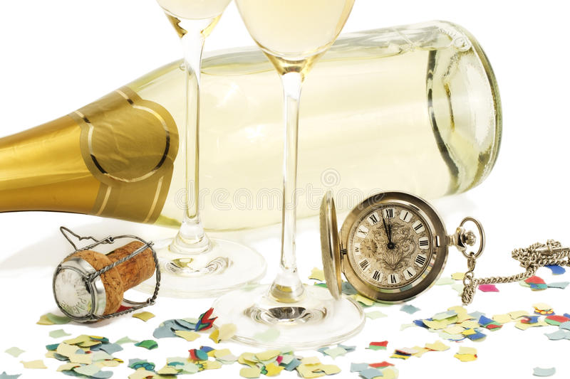 Two glasses with champagne, old pocket watch, cork. And confetti in front of a champagne bottle on white background royalty free stock image