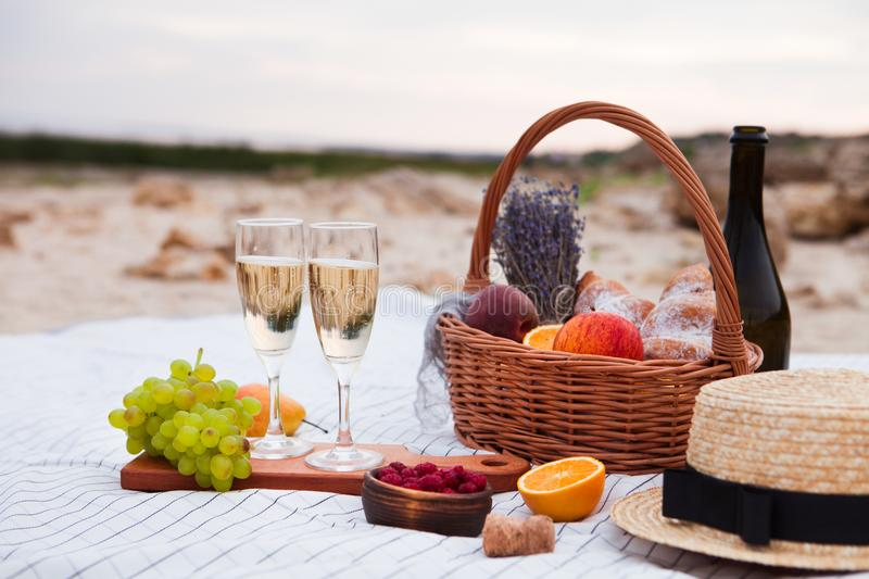 Two glasses of champagne. Picnic on the beach at sunset in the w stock photo