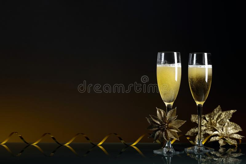 Two glasses of champagne ready to bring New Year on a black background royalty free stock photos