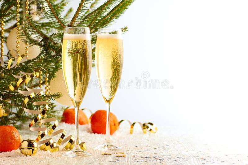 Two glasses of champagne ready to bring New Year on Christmas tree background royalty free stock photography