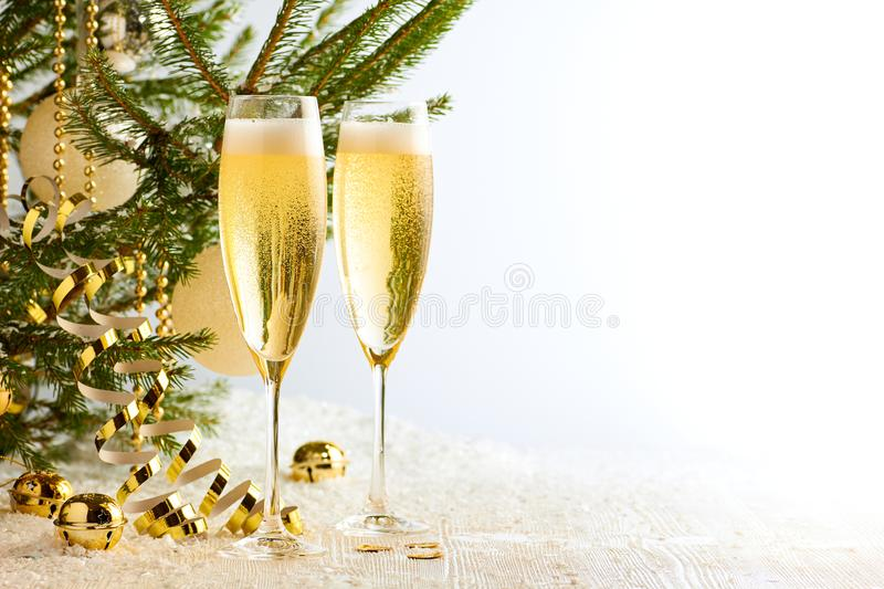 Two glasses of champagne ready to bring New Year on Christmas tree background stock photos