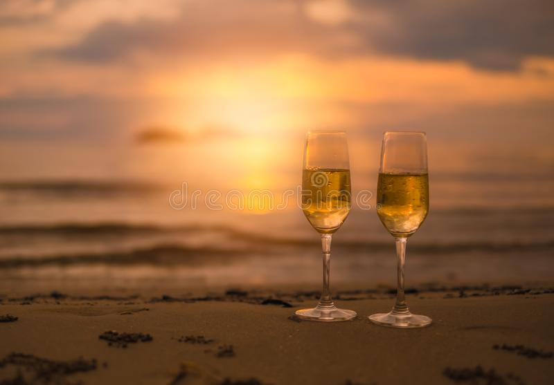 Two glasses of champagne on sandy beach in sunset. Two glasses of champagne on sandy beach  in beautiful sunset stock photos