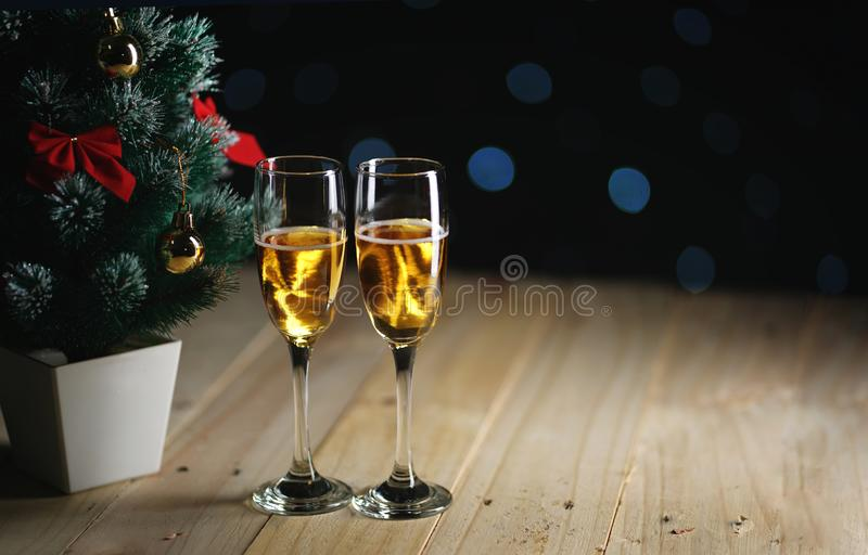 Two Glasses of Champagne Beside Small Christmas Tree Dark Glow L royalty free stock images
