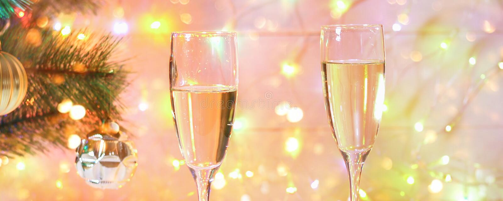 Two glasses of champagne stand on a white wooden table on the background of a New Year tree and garlands. Christmas bokeh. royalty free stock photography