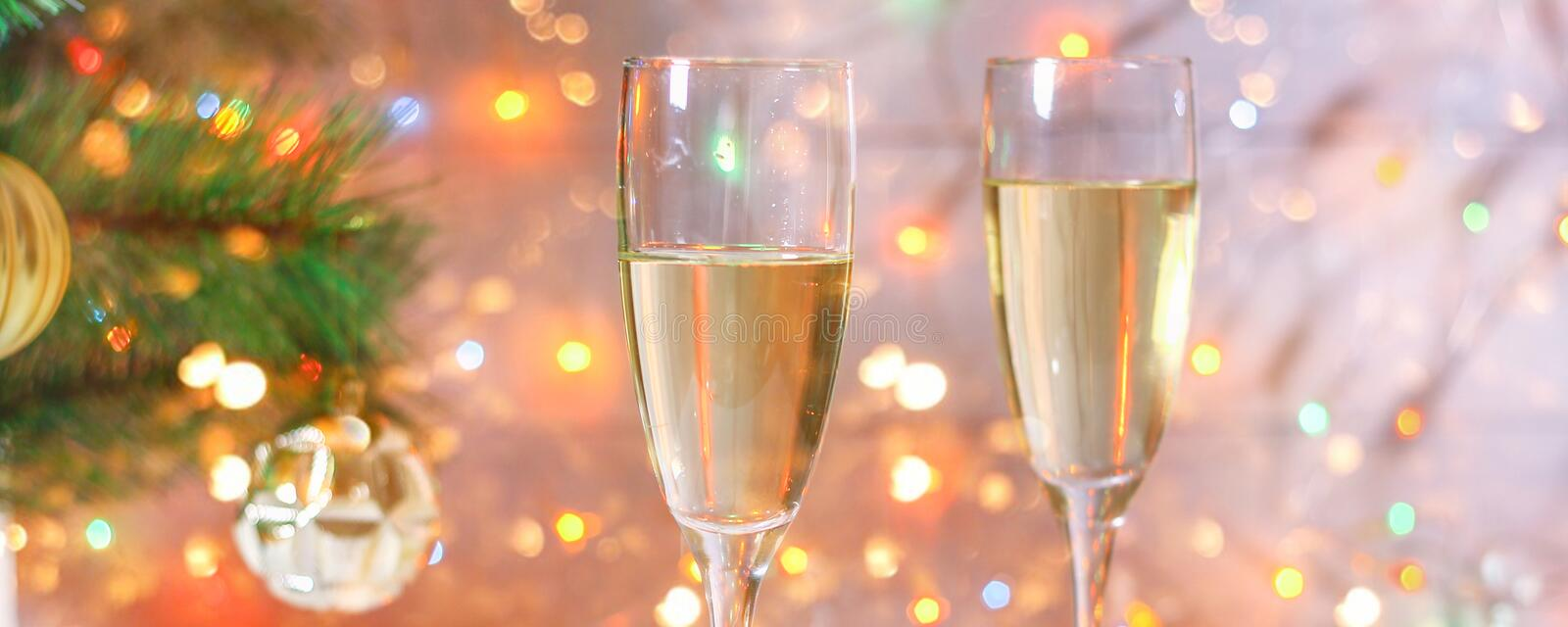 Two glasses of champagne stand on a white wooden table on the background of a New Year tree and garlands. Christmas bokeh. Two glasses of champagne stand on a stock photography