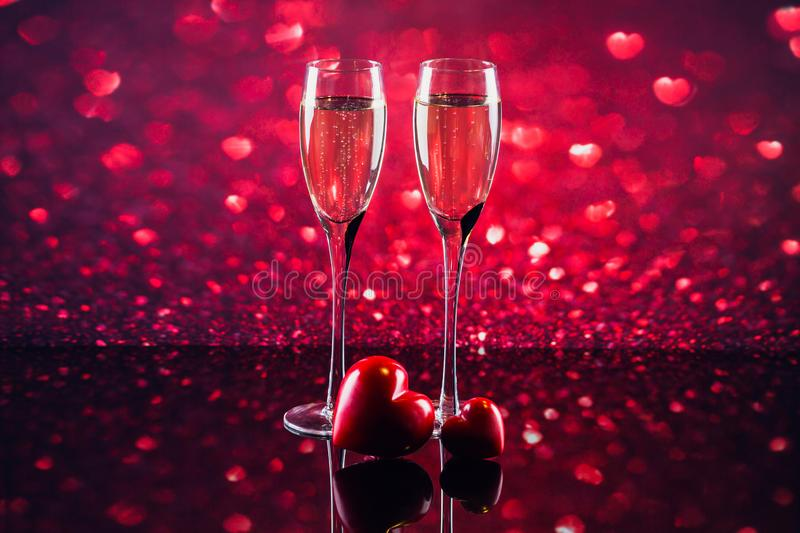 Two glasses of champagne with red heart shape bokeh on background stock images