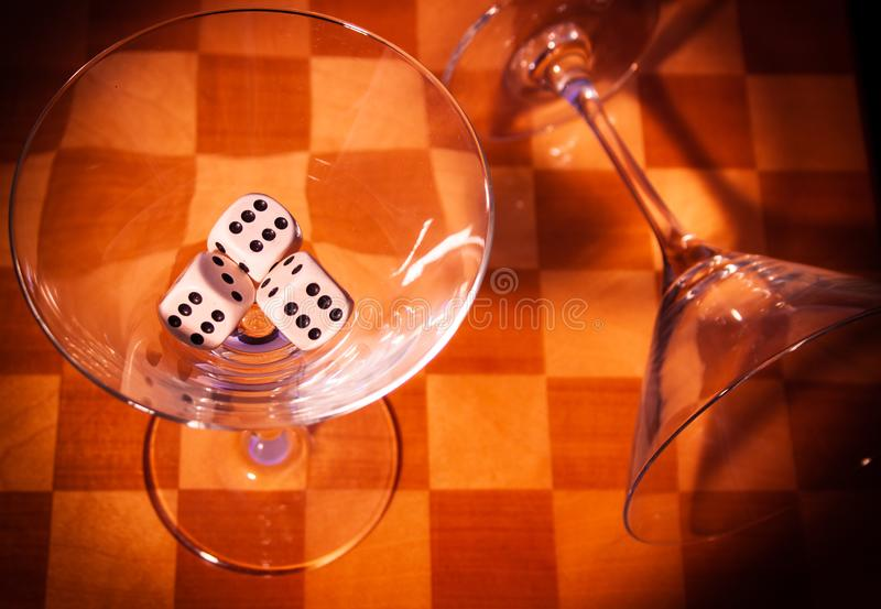 Two glasses on a chessboard. With three dices with shadows royalty free stock photo