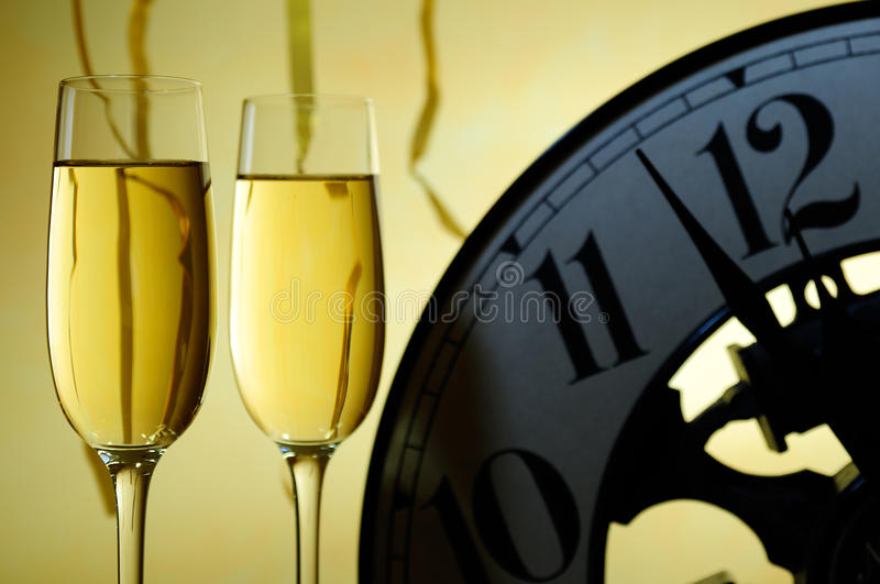 Two glasses and a clock ready for a new year stock photography