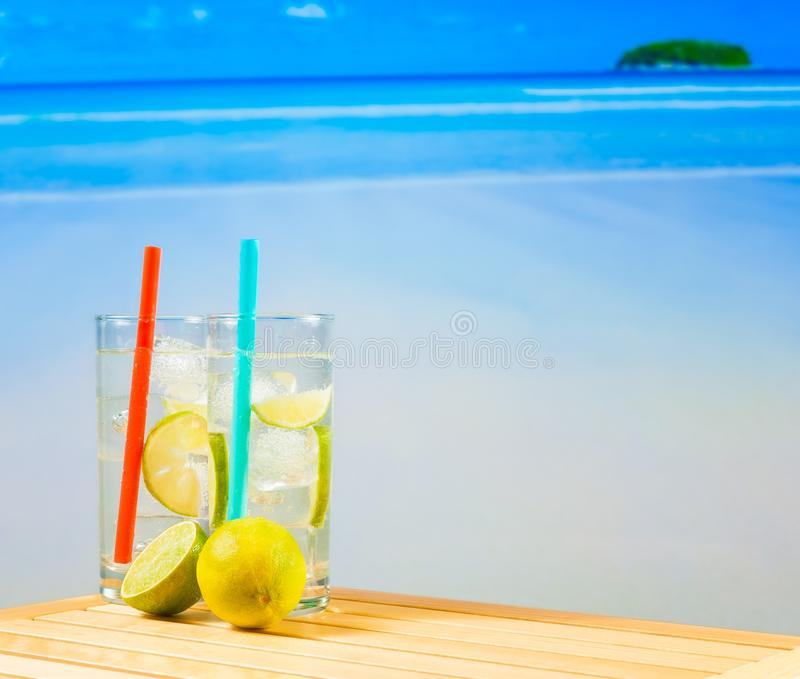 Two Glasses Of Cocktail With Lime Slice On Blur Beach Stock Photo