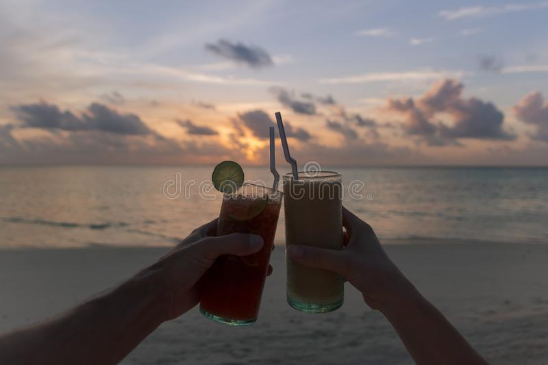 Two hands clinking cocktails during a sunset on the beach. Tropical island vacation. Happy Hour stock image