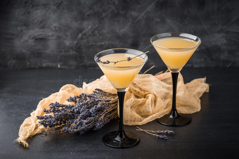 Two glasses with a cocktail martini. Lemonade martini with lavender on dark background stock image