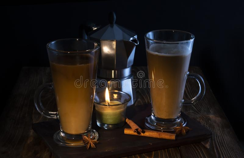 Two glasses of coffee with a coffee maker in the background on a wooden table with chocolate, anise, karatz lit by candle flame stock image