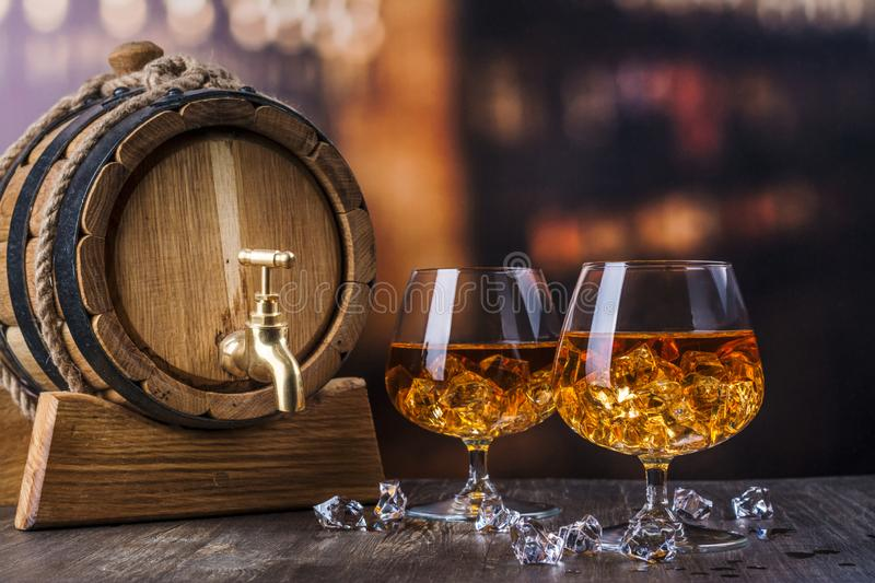 Two glasses of Cognac with ice cubes stock photos