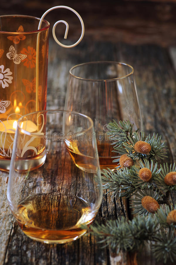 Two glasses of cognac, pine branches and burning candle. Winter mood: Two glasses of cognac, pine branches and burning candle royalty free stock photography