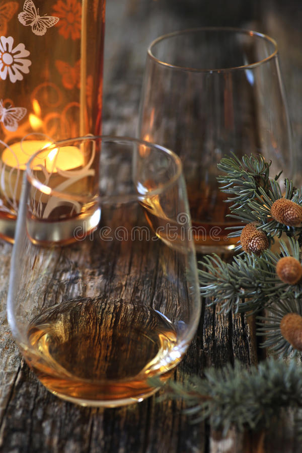 Two glasses of cognac, pine branches and burning candle. Winter mood: Two glasses of cognac, pine branches and burning candle. Toned imade. Focus selective royalty free stock images