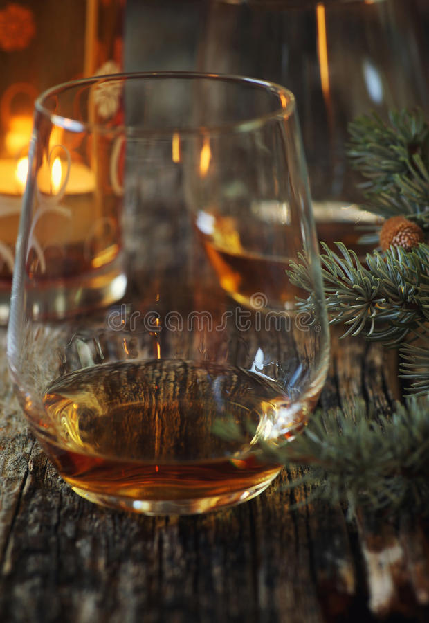 Two glasses of cognac, pine branches and burning candle. Winter mood: Two glasses of cognac, pine branches and burning candle. Toned image. Focus selective stock image