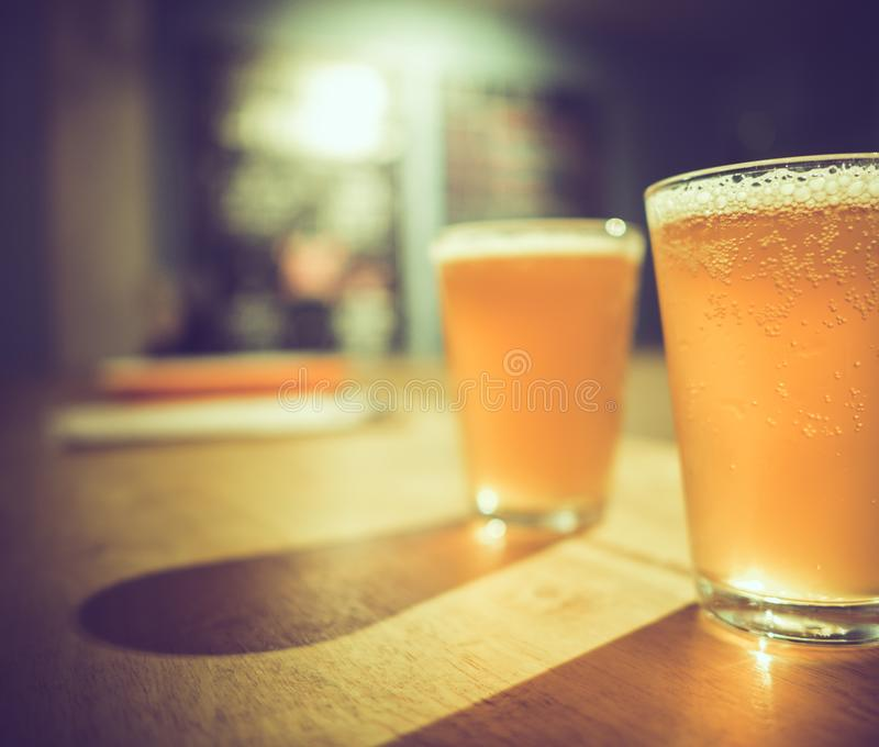 Two glasses of cold craft beer with white bubbles and shadow on wooden table at bar, vintage dark tone royalty free stock photos