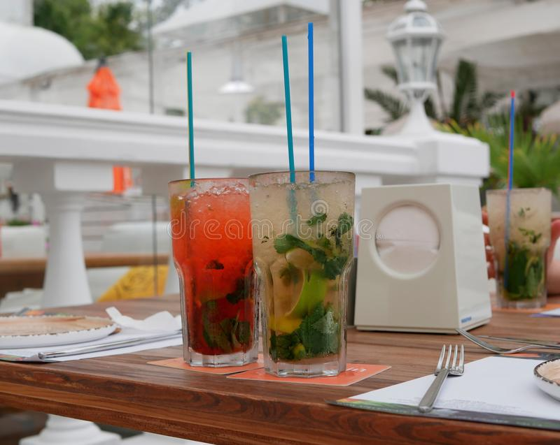 Two glasses of cold mojitos and an iced strawberry cocktail sit on a table on the cafe`s summer veranda. Glasses with a tube cover stock images