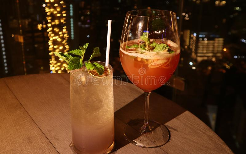 Two glasses of different type of cocktail at the rooftop bar with bokeh lights in background stock photography