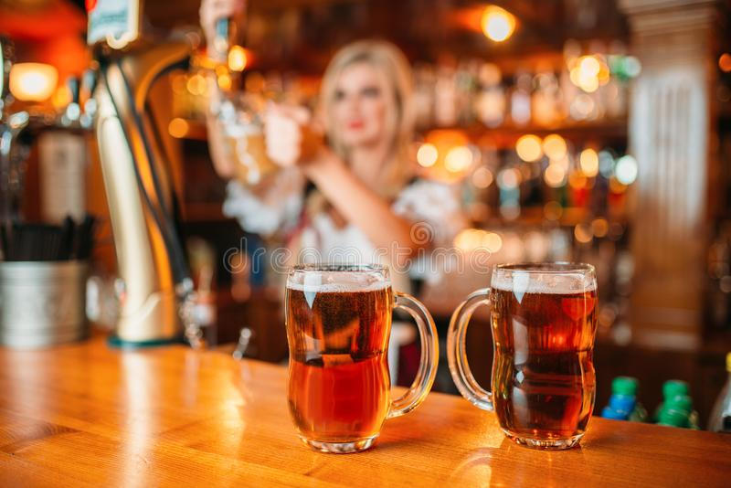Two glasses of fresh beer on counter, octoberfest. Two glasses of fresh beer on counter, sexy waitress pours foamy beverage into a mug in pub. Octoberfest royalty free stock photos