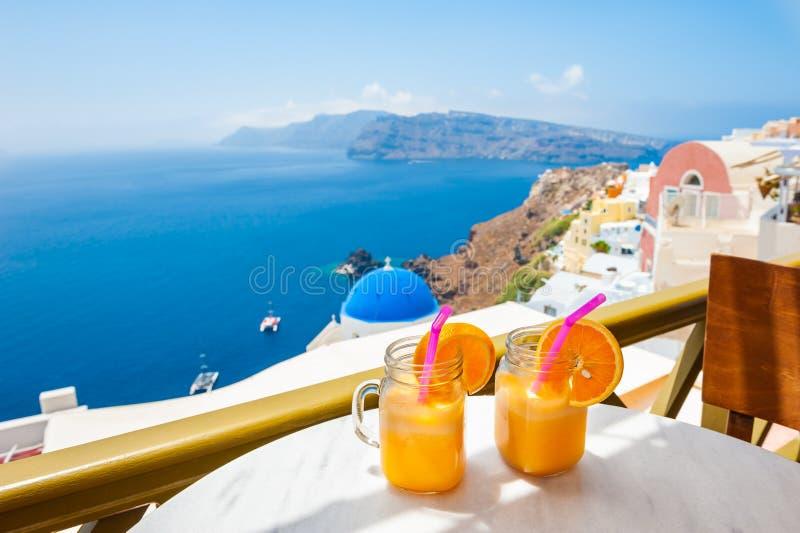 Two glasses of fresh orange juice on the table. Santorini island, Greece royalty free stock image