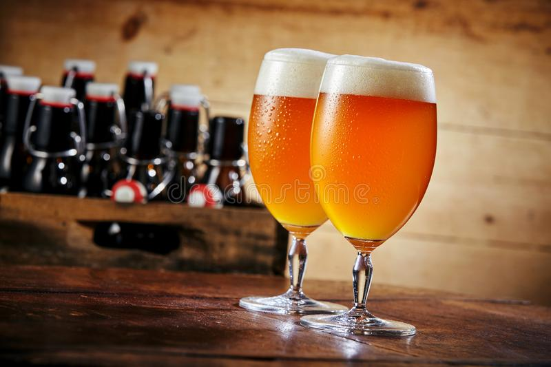 Two glasses of beer standing on wooden table royalty free stock photos