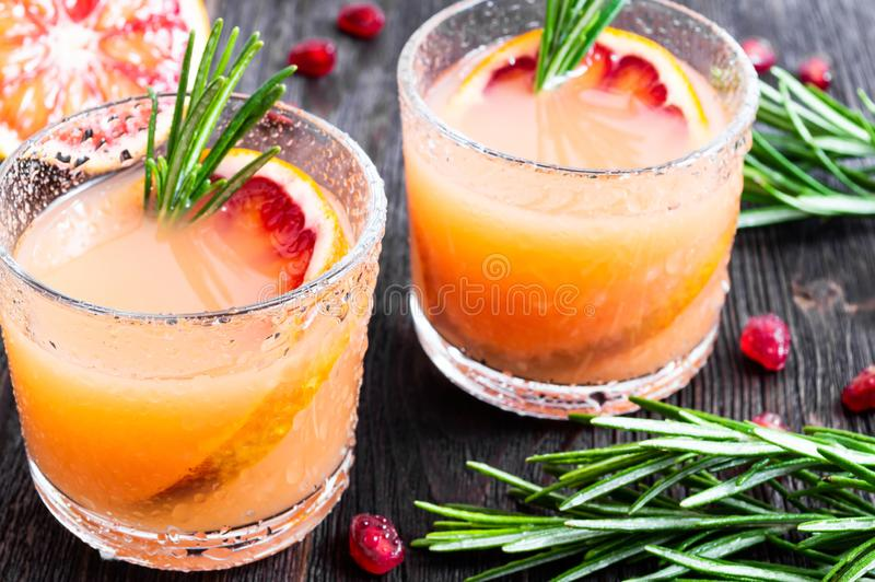 Two glasses of fresh summer drink with blood orange and rosemary on a dark wooden background. Selective focus royalty free stock image