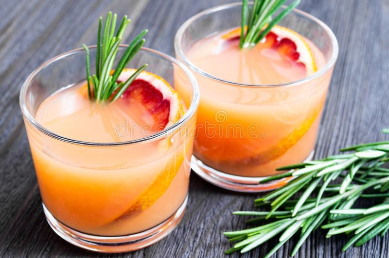 Two glasses of fresh summer drink with blood orange and rosemary on a dark wooden background. Selective focus royalty free stock photography