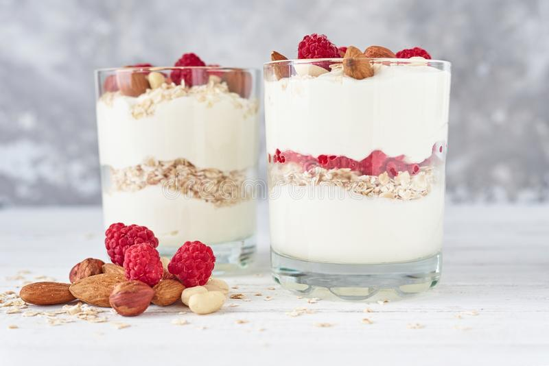 Two glasses of greek yogurt granola with raspberries, oatmeal flakes and nuts on a white background. Healthy nutrition stock photo